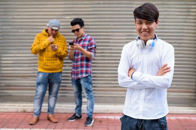 Portret trzech młodych mężczyzn azjatyckich stojących przed drzwiami magazynu na ulicach bangkoku w tajlandii