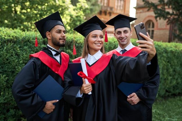 Portret trzech młodych międzynarodowych przyjaciół absolwentów robiących selfie w szatach dyplomowych w kampusie.