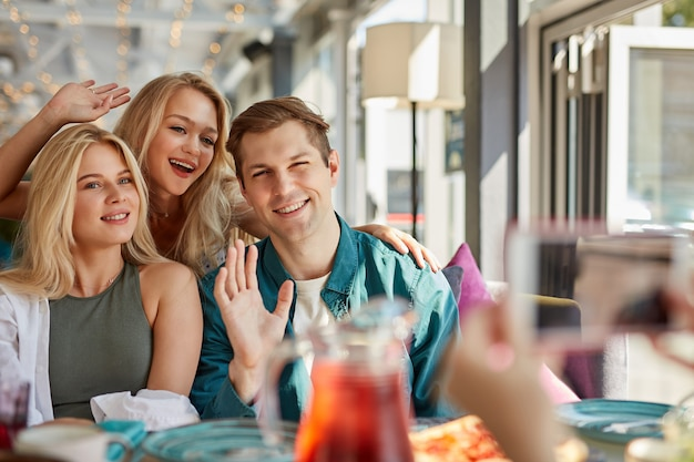 Portret trzech młodych najlepszych przyjaciół siedzi w kawiarni