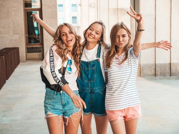 Portret trzech młodych pięknych uśmiechniętych hipster dziewcząt w modne letnie ubrania. seksowne beztroskie kobiety pozowanie na ulicy. pozytywne modele zabawy. podnoszą ręce