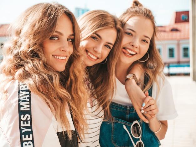 Portret trzech młodych pięknych uśmiechniętych hipster dziewcząt w modne letnie ubrania. seksowne beztroskie kobiety pozowanie na ulicy. pozytywne modele zabawy. przytulanie