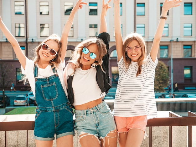 Portret trzech młodych pięknych uśmiechniętych hipster dziewcząt w modne letnie ubrania. seksowne beztroskie kobiety pozowanie na ulicy. pozytywne modele zabawy w okularach przeciwsłonecznych. przytulanie i podnoszenie rąk