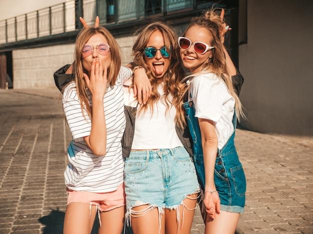 Portret trzech młodych pięknych uśmiechniętych hipster dziewcząt w modne letnie ubrania. seksowne beztroskie kobiety pozowanie na ulicy. pozytywne modele zabawy w okularach przeciwsłonecznych. przytulanie i pokazywanie języka