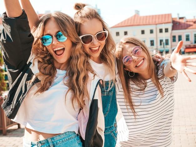 Portret trzech młodych pięknych uśmiechniętych hipster dziewcząt w modne letnie ubrania. seksowne beztroskie kobiety pozowanie na ulicy. pozytywne modele zabawy w okularach przeciwsłonecznych. przytulanie