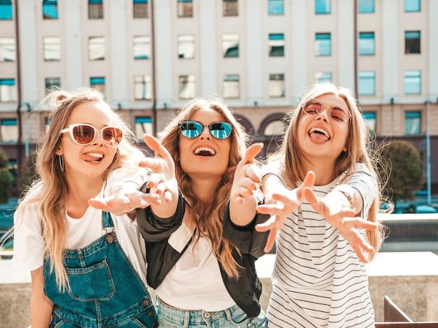Portret trzech młodych pięknych uśmiechniętych hipster dziewcząt w modne letnie ubrania. seksowne beztroskie kobiety pozowanie na ulicy. pozytywne modele zabawy. wyciągają ręce do aparatu
