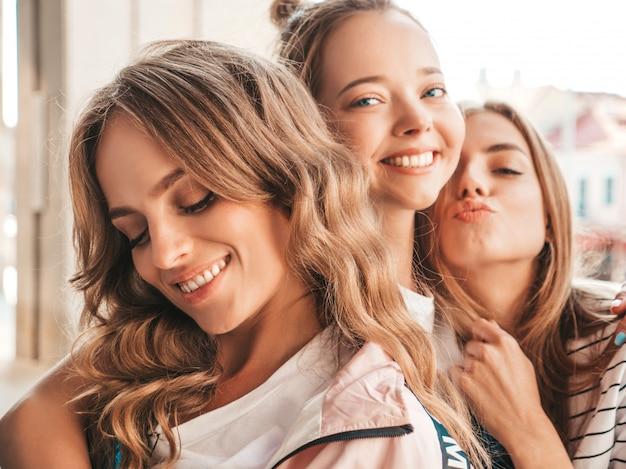 Portret trzech młodych pięknych uśmiechniętych hipster dziewcząt w modne letnie ubrania. seksowne beztroskie kobiety pozowanie na ulicy. pozytywne modele zabawy