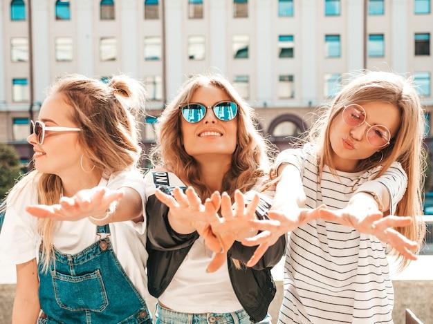 Portret trzech młodych pięknych uśmiechniętych hipster dziewcząt w modne letnie ubrania. seksowne beztroskie kobiety pozujące na ulicy. pozytywne modele zabawy w okularach przeciwsłonecznych. pokazują swoje dłonie