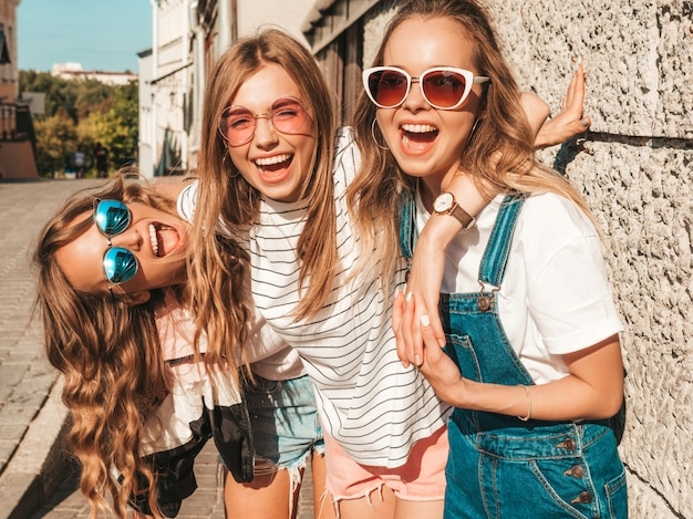 Portret trzech młodych pięknych uśmiechniętych hipster dziewcząt w modne letnie ubrania. seksowne beztroskie kobiety pozuje blisko ściany na ulicie. pozytywni modele ma zabawę w okularach przeciwsłonecznych
