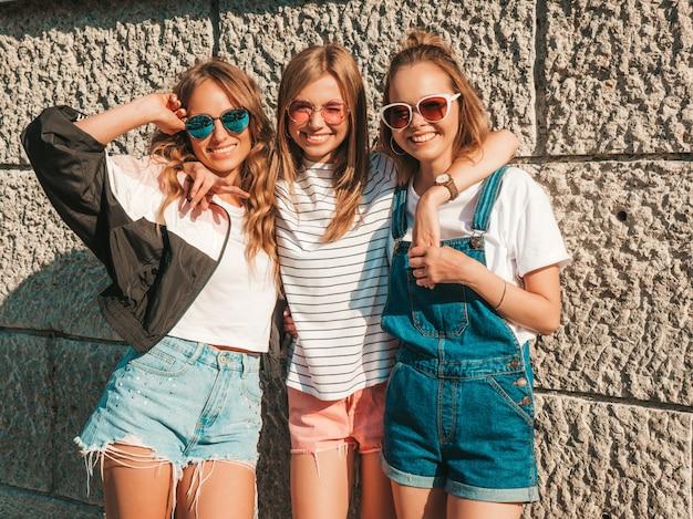 Portret trzech młodych pięknych uśmiechniętych hipster dziewcząt w modne letnie ubrania. seksowne beztroskie kobiety pozuje w ulicznej pobliskiej ścianie. pozytywni modele ma zabawę w okularach przeciwsłonecznych przytulenie