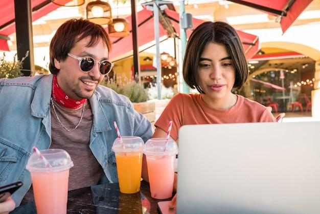 Portret trzech młodych przyjaciół za pomocą laptopa siedząc na zewnątrz w kawiarni. koncepcja przyjaźni i technologii.