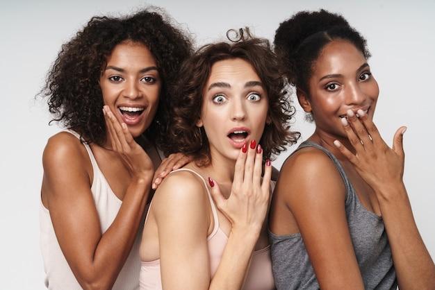 Portret trzech młodych wieloetnicznych kobiet patrzących na kamerę ze zdziwieniem