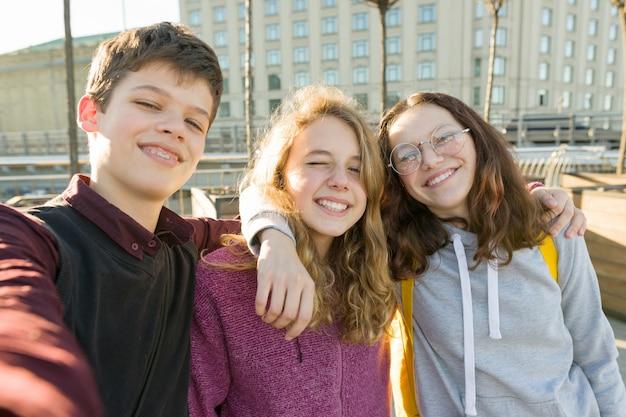 Portret trzech nastoletnich przyjaciół chłopca i dwóch dziewczynek, uśmiechając się i biorąc selfie na zewnątrz.