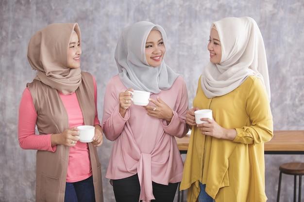 Portret trzech pięknych muzułmańskich kobiet stojących mając razem czas kawy