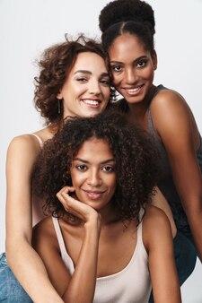 Portret trzech pięknych, wieloetnicznych kobiet stojących razem i uśmiechających się do kamery