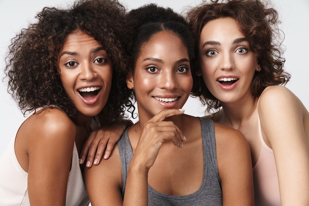 Portret trzech pięknych wielorasowych kobiet stojących razem i uśmiechających się do kamery