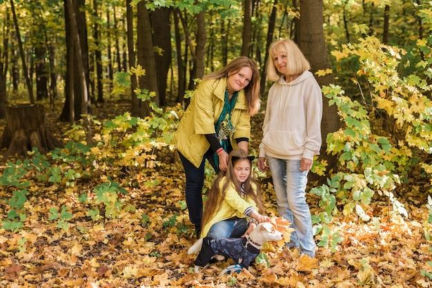 Portret trzech pokoleń szczęśliwej pięknej kobiety i psa w jesiennej przyrodzie