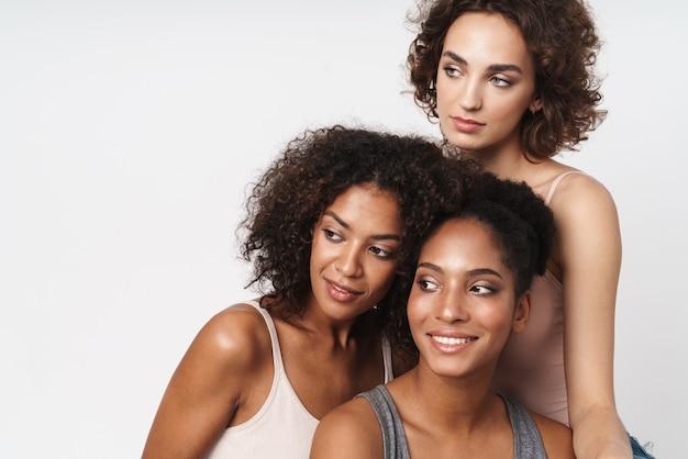 Portret trzech radosnych wielorasowych kobiet uśmiechających się i patrzących na bok