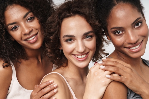 Portret trzech szczęśliwych wieloetnicznych kobiet przytulających się i uśmiechających się do kamery