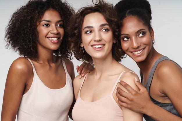 Portret trzech szczęśliwych wieloetnicznych kobiet uśmiechających się i patrzących na bok