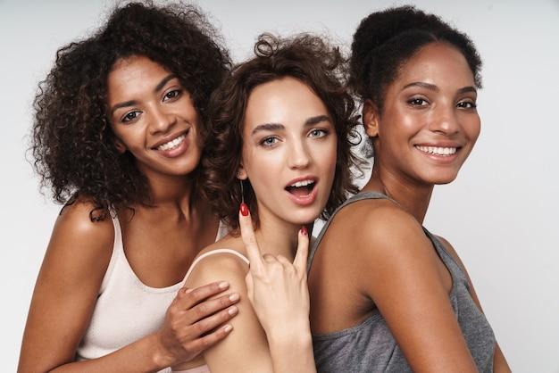 Portret trzech szczęśliwych, wieloetnicznych kobiet, uśmiechających się i pokazujących palce rogów