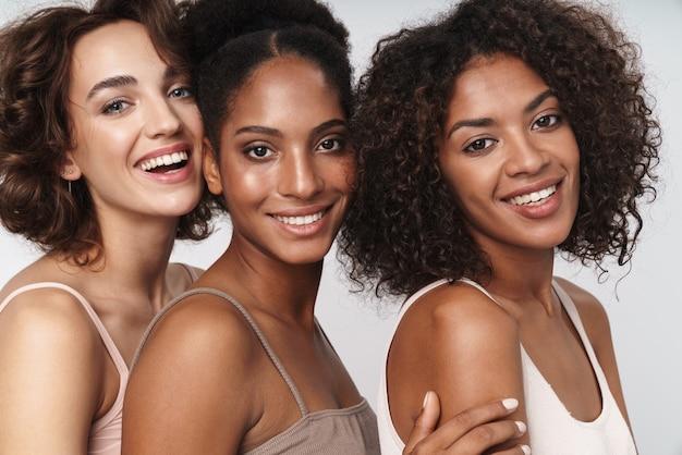 Portret trzech uroczych wieloetnicznych kobiet stojących razem i uśmiechających się do kamery