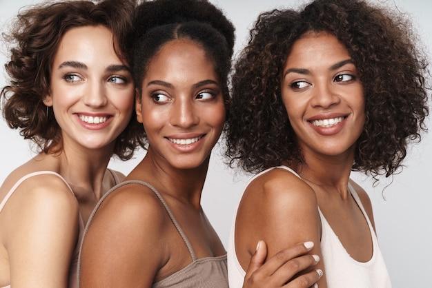Portret trzech uroczych, wieloetnicznych kobiet uśmiechających się i patrzących na bok
