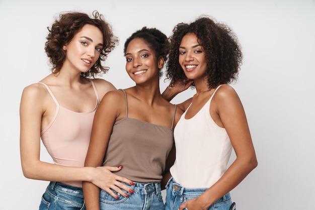 Portret trzech uwodzicielskich, wieloetnicznych kobiet stojących razem i uśmiechających się do kamery
