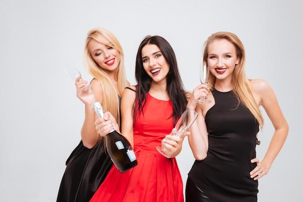 Portret trzech wesołych pięknych młodych kobiet w okularach i butelce szampana na białym tle