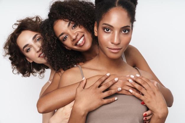 Portret trzech wesołych, wieloetnicznych kobiet, uśmiechniętych i przytulających się razem