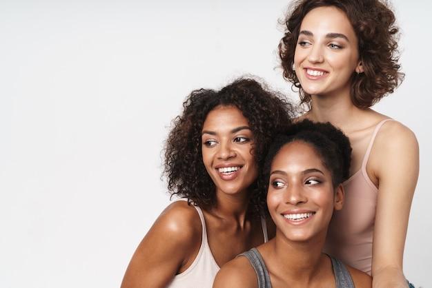 Portret trzech wesołych wielorasowych kobiet uśmiechających się i patrzących na bok