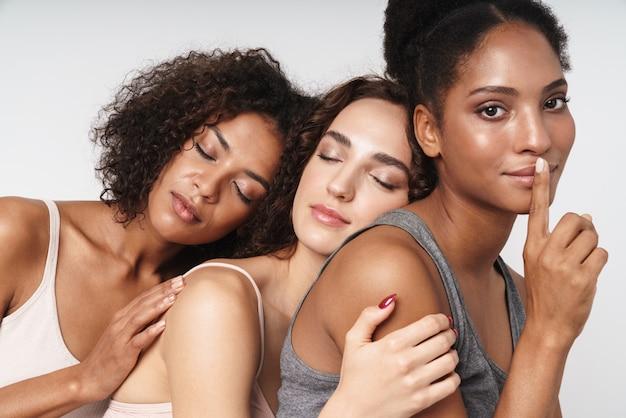 Portret trzech wspaniałych, wieloetnicznych kobiet pokazujących cii palec podczas wspólnego przytulania