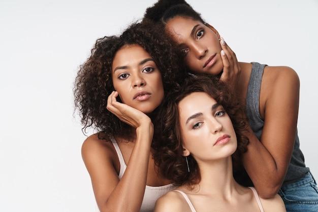 Portret trzech wspaniałych wieloetnicznych kobiet stojących razem i patrzących na kamerę