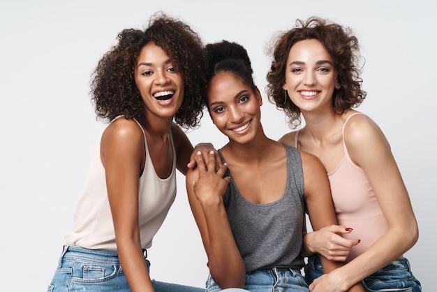 Portret trzech wspaniałych wielorasowych kobiet stojących razem i uśmiechających się do kamery