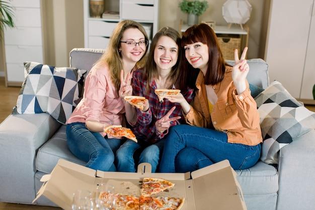 Portret trzy szczęśliwego młodego żeńskiego przyjaciela je pizzę na kanapie w domu w przypadkowych ubraniach. przyjaźń kobiet, wspólne jedzenie