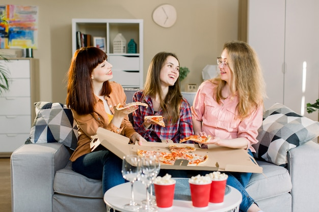 Portret trzy szczęśliwej młodej dziewczyny je pizzę na kanapie w domu. piękne damy uśmiechające się i komunikujące o życiu codziennym: pracy, domu, mężczyznach.