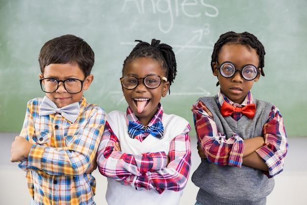 Portret trzy szkolnego dzieciaka stoi przeciw chalkboard