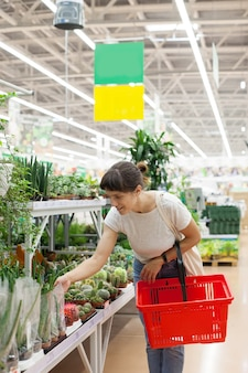 Portret trzydziestoletniej dziewczyny w supermarkecie w pobliżu działu z doniczkowymi kwiatami w pomieszczeniach