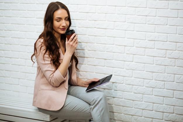 Portret trzyma cyfrową pastylkę w biurze szczęśliwy bizneswoman, pije kawę