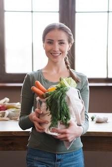 Portret trzyma organicznie warzywa pozytywna młoda kobieta