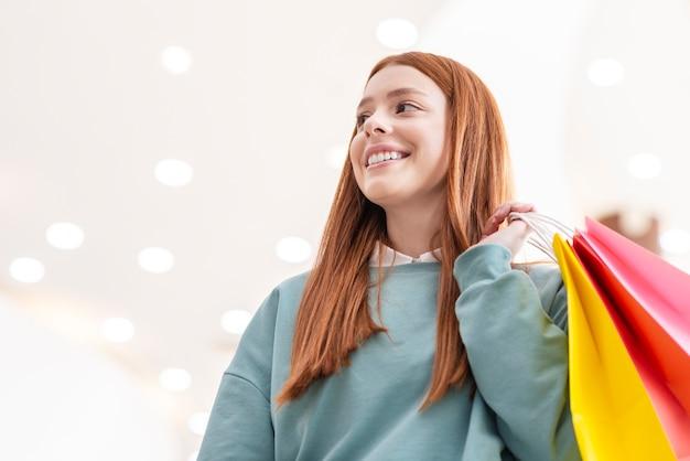 Portret trzyma papierowe torby uśmiechnięta dama