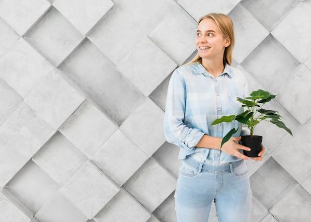 Portret trzyma rośliny pozytywna młoda kobieta