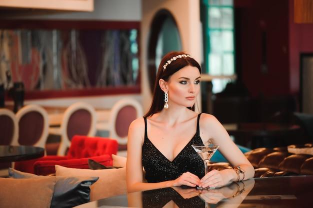 Portret trzyma szklankę martini piękna kobieta.