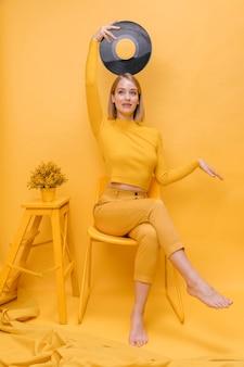 Portret trzyma winyl w żółtej scenie kobieta