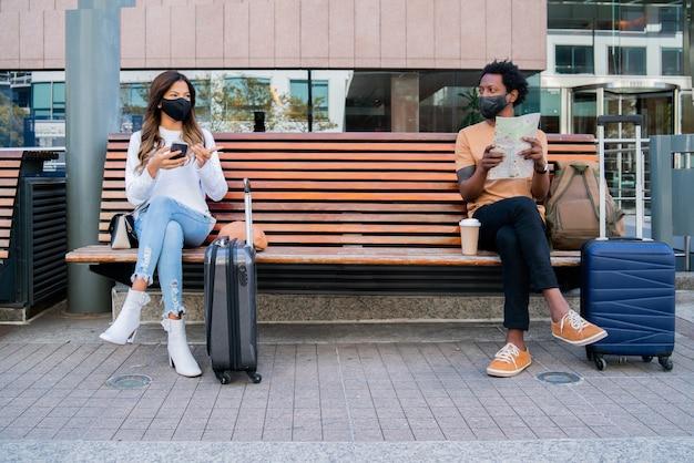 Portret turystów czekających poza lotniskiem lub dworcem kolejowym, siedząc na ławce i zachowując odległość