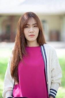 Portret twarz pięknej azjatyckiej młodszej kobiety stojącej na zewnątrz
