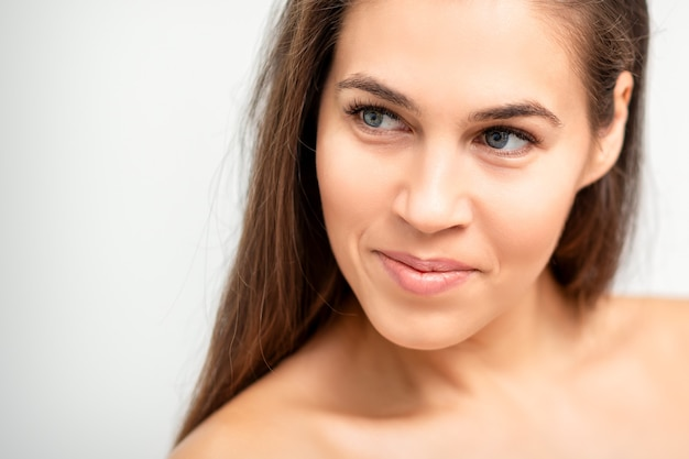 Portret twarzy młodej kobiety rasy kaukaskiej z nagimi ramionami i naturalnym makijażem na białej ścianie