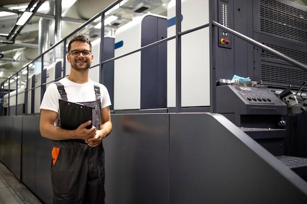 Portret typografa stojącego przy nowoczesnej maszynie offsetowej kontrolującej proces druku
