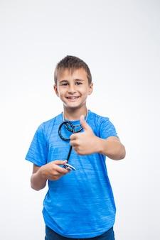 Portret uśmiechnięta chłopiec gestykuluje aprobaty z stetoskopem