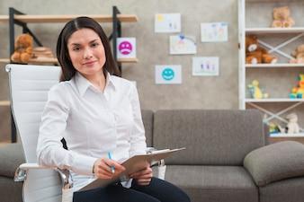 Portret uśmiechnięty żeński psychologa obsiadanie na białym krześle z schowkiem i ołówkiem w jej biurze