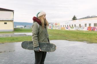 Portret uśmiechnięty młodej kobiety mienia deskorolka w parku